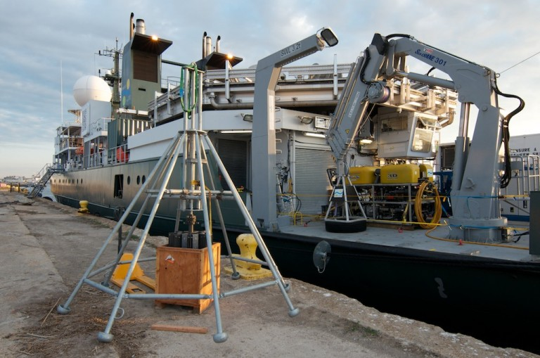 Scientists assemble the multicore instrument from shipping containers on the dock before loading it onto R/V Falkor.