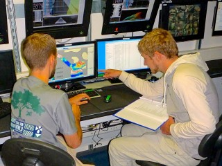 Brian Shiro (left) and Jonathan Tree (right) in the control room discussing incoming magnetometer data.