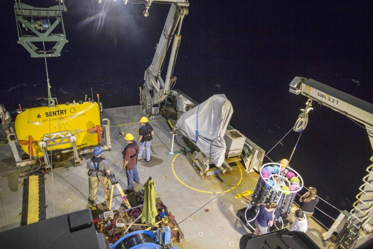 The autonomous underwater vehicle Sentry (yellow, at left) is prepared for deployment off the stern of the R/V Falkor, after a trace-metal CTD instrument package and water sampler is recovered (lower right).