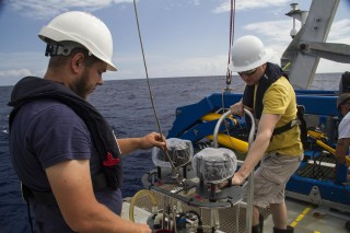 The McLane pumps are part of the technology being used to get samples from the depths of the ocean. Here being deployed by deckhand Hans Schonherr and analytical chemist Matt McIlvin.