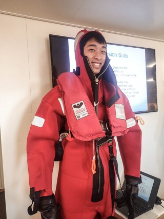 One of the many things Caleb has had the opportunity to learn and experience: safety drills before sailing. Here he learns how to proper prepare and wear an emrgency immersion suit.