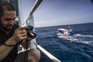 Captain Phillip Gunther snaps a couple of pictures as fishermen come close to say hello
