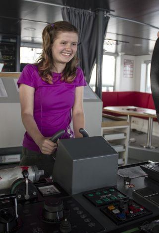 Riannon smiles while she learns a little bit about driving a research vessel