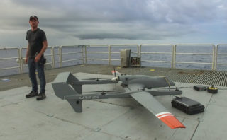 Scott Brown, Physicist and Engineer, stands next to one of the HQ-60B drones to scan the sea surface. The drone had just completed another successful mission and was being disarmed on Falkor's flight deck.