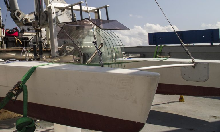 Rotating glass plates in the remotely operated catamaran dip into the water allowing the oily microlayer to stick to them. The film is wiped into a container.