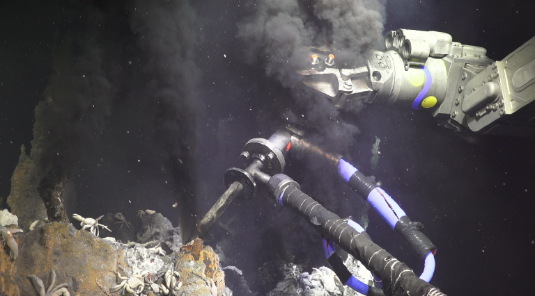 ROV pilots guide the fluid sampler to the perfect spot in the chimney.