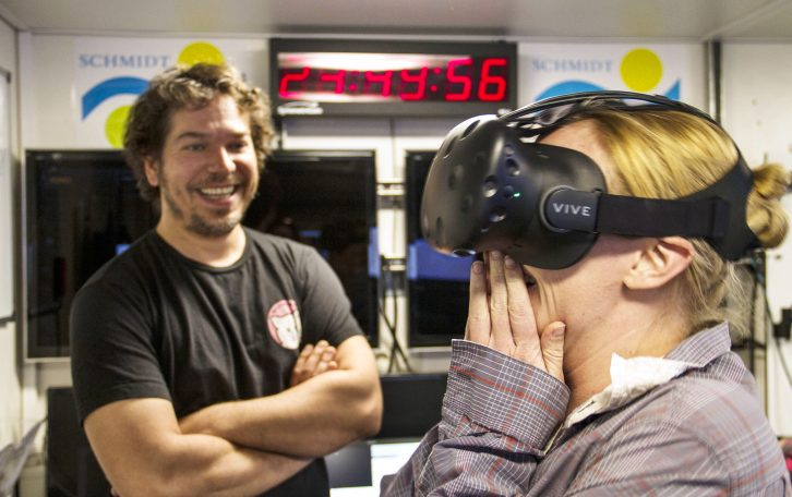 Ben Knorlein, Computer Scientist, observers Melissa Omand as she reacts to the first Virtual Reality experience created on board Falkor from holographic images of plankton suspended in the water.