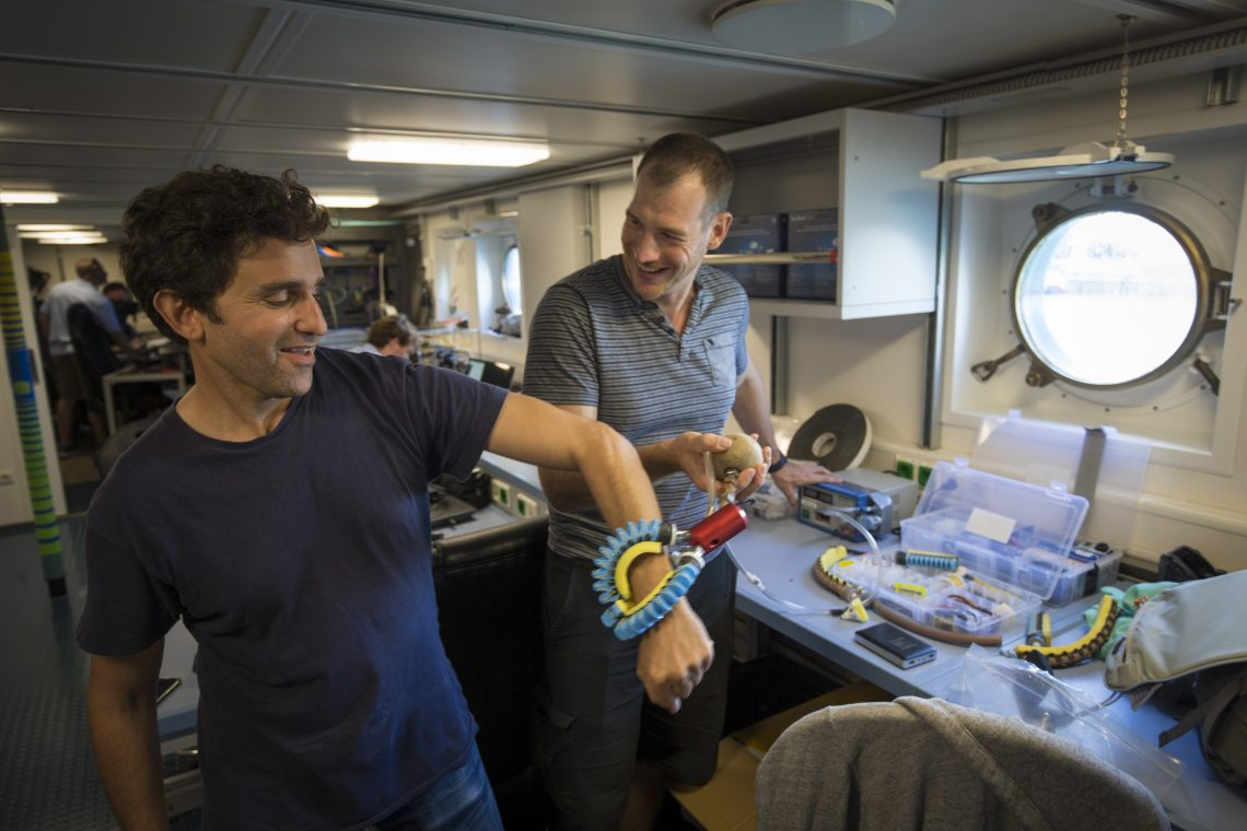 Daniel Vogt tests the newly engineered 'squishy fingers' on David Gruber. These will be used to gently interact with the coral and creatures of the deep ocean.