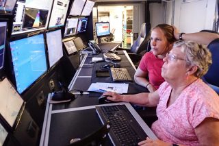 Jena Kline is a teacher from 'Iolani School currently onboard Falkor to learn about multibeam mapping. Joyce Miller teaches her how to clean noise out of data in order to render more reliable maps.