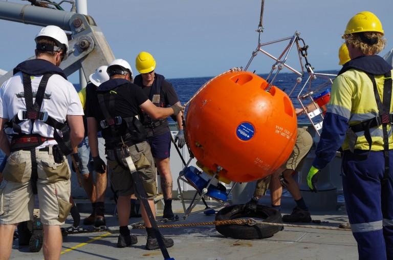 Crew and Scientists lower an Acoustic Doppler Current Profiler (ADCP) to the deck of the Falkor.