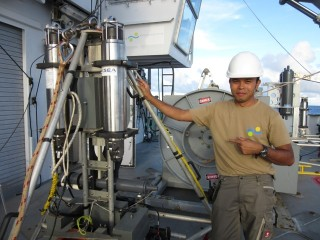 Deckhand Archel stands next to one of the landers that are carefully released into the Mariana Trench and brought back onto Falkor.