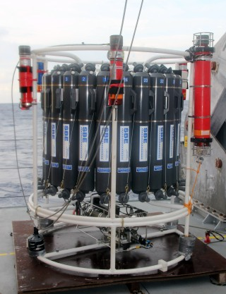 "The grey cylinders with ""SBE"" on the side and numbered 1-24 around the top are the water samplers we use to collect seawater at specific depths in the ocean. The bright red ""canisters"" mounted on the outside are the navigation beacons we were testing. When we start work, we will have one of these on the CTD at all times, and another on Nereus, so that we can know – very accurately – where any of our instruments are at depth. For example, in today's cast, while we lowered the CTD over the back of the ship it did not go straight down, vertically. Instead, because of the strong currents, by the time the CTD was at 2400m depth it was also 120m astern of the ship or, for scale, about 1 and a half times the length of the ship away."