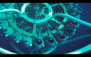 Video still of CTD rosette gathering water sample at depth.