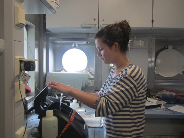 Danielle Mitchell loading a sample into a fluorometer to measure chlorophyll.