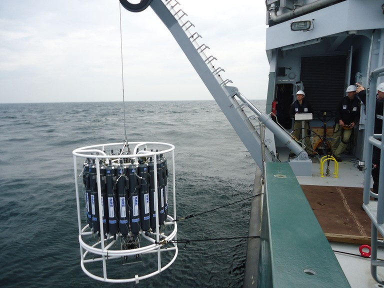 The 24-bottle CTD rosette being launched over the side of the R/V Falkor. The rosette will be used to collect water samples throughout the water column at various depths.