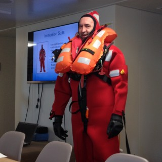 Safety first! Cruise leader Professor Grey Ivey volunteered to demonstrate the immersion suit