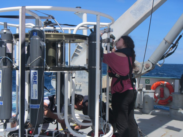 Gabi Pilo (right), Spencer Kawamoto and Ryan McDougall-Fisher take instruments off the CTD-cage on a rare sunny day during the transit to Hobart.