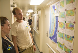 Crew members discuss where to place their bets while studying the maps of the 10 back-arc segments posted in the main hallway of R/V Falkor.