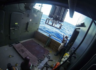 The CTD instrument package on R/V Falkor is lifted over the side for a test deployment.