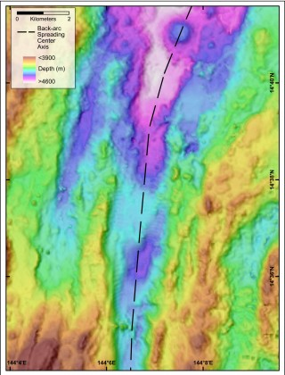 Map of a section of the Mariana Back-arc. The black dashed line traces the axis of spreading, which has created a valley up to 10 km wide in this location. This valley is one of our targets for the discovery of hydrothermal vents.