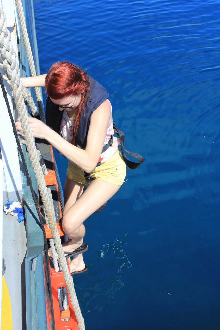 Jennifer climbs down Falkor into the work boat, Atrayu.