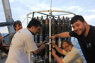 Chief scientist Brian Glazer and Schmidt Ocean Institute marine technicians James Cooper, Pete Keen, and Leighton Rolley attach a new ph. sensor to the CTD Rosette.