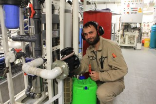 Electro technical officer Todor Gerasimov works on fixing a fresh water flow sensor.
