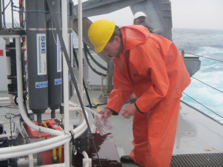 Peter Strutton transferring water samples collected in the Niskin bottles.
