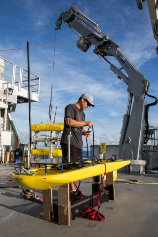"effery Oshiro prepares the ""Float"" portion of the Wave Glider on the aft deck of Falkor while on the Coordinated Robotics cruise."