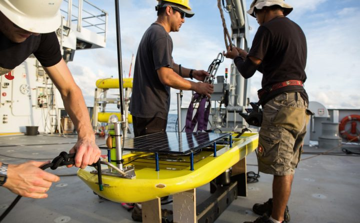 Oliver Hurdwell, Jeffery Oshiro, and Archel Benitez ready the glider to be launched into the water using Falkor's aft deck cranes.