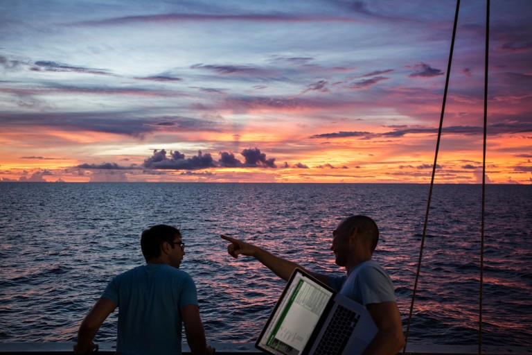 Scientists take a break from their labs to enjoy a spectacular sunset off the aft deck of Falkor.