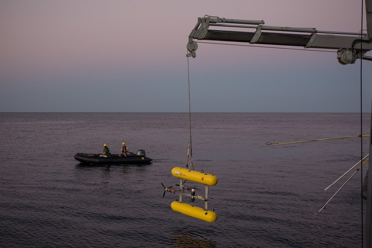 Professor Stefan Williams and Deckhand Erik Suits watch from a zodiac as AUV Sirius is recovered to the aft deck.