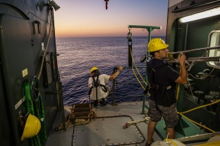 Angelos Mallios helps load in AUV's as dusk falls.